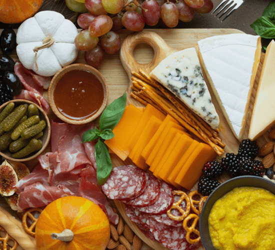 An aerial view of a chartcuterie board with an assortment of cheeses, meats and fruits.