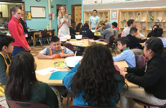 Teachers and students in a classroom working at tables