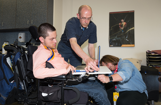 two people work to instal a device on a man's wheelchair